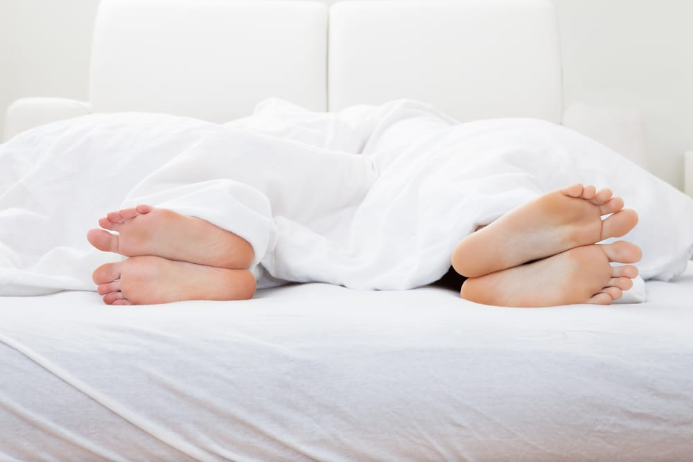 Close-up of couple's feet sleeping on bed in bedroom