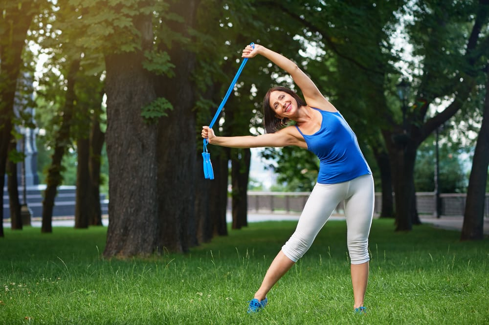Happy middle aged caucasian brunette woman in blue sportswear stretching with blue jumping rope over her head outdoors smiling