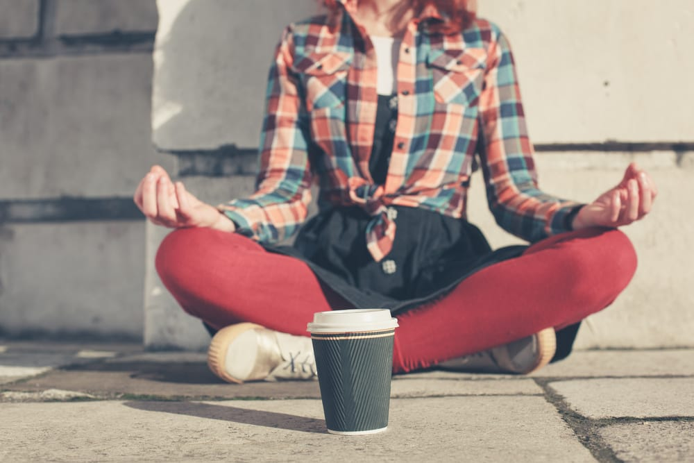 A young woman is sitting and meditating in the street