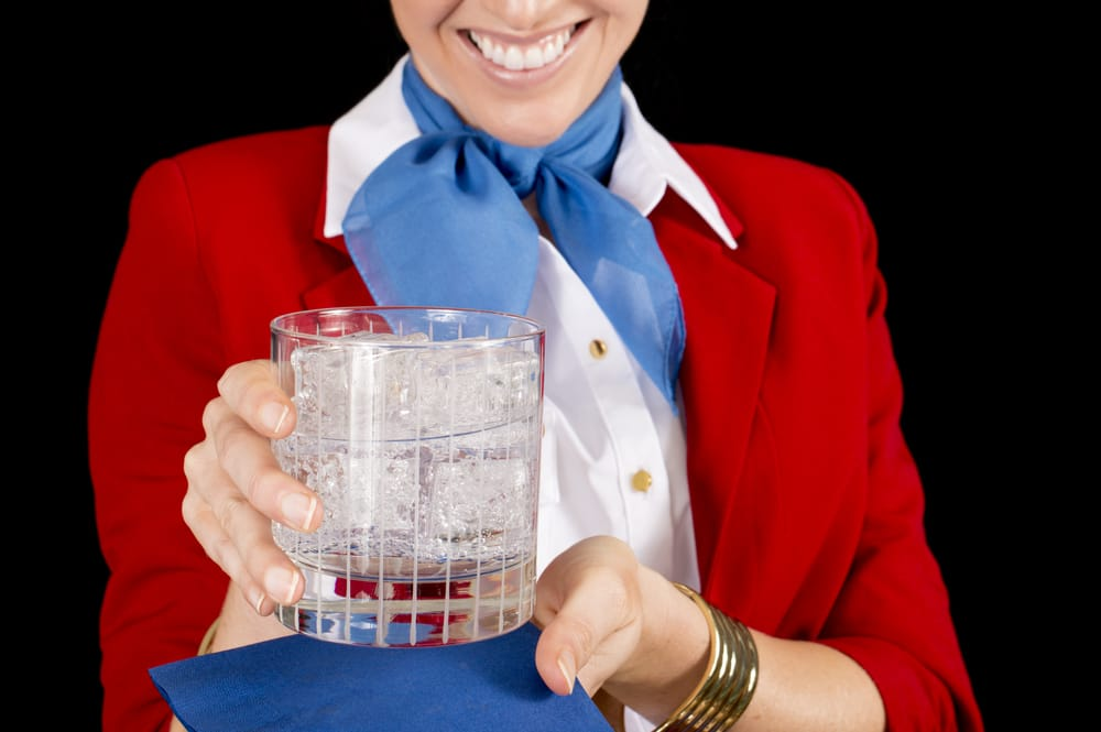 An unidentifiable flight attendant or restaurant server offering a refreshing beverage. Focus on the drink.