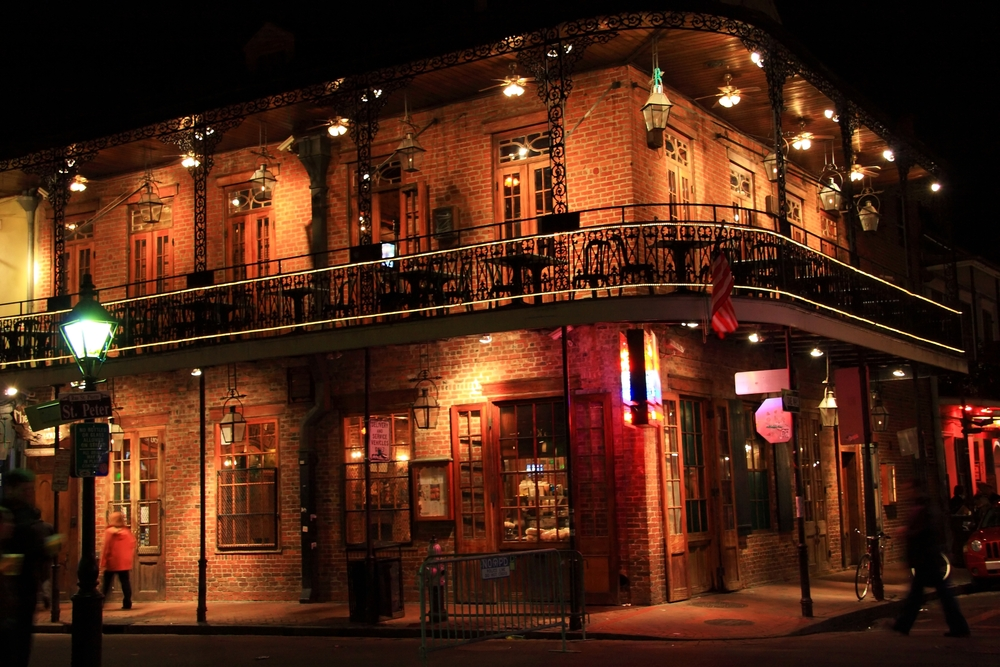 1_Brick building with balcony on the corner of St. Peter and Bourbon Streets at night in the French Quarter of New Orleans, LA