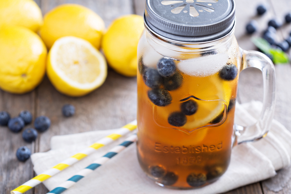 FCOM - Ice tea in mason jar mug with lemon and blueberries refreshing in hot summer day